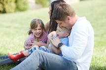 a loving family sitting in grass