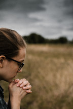 a woman praying in a field