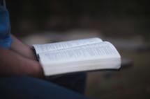 Holding an open Bible.