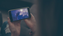 a woman watching a worship service streamed to her phone