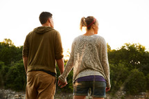 a couple walking outdoors holding hands