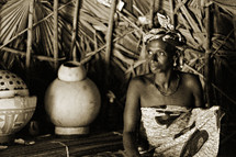 African woman in her hut  by her pottery