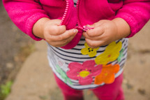 a toddler zipping her jacket