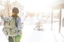Woman with backpack facing a snow-covered day.