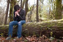 Man in prayer sitting on fallen tree in the woods.
