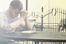 man with tattoos praying