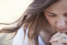 Closeup of a woman in reverent prayer.
