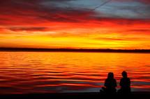 silhouettes sitting on a beach