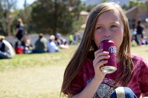 a child drinking a soda at an outdoor festival