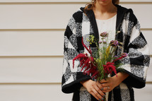 a woman holding a fall bouquet