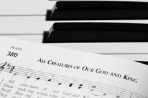 All Creatures of Our God and King sheet music on a piano