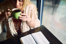 a woman drinking coffee and an open Bible