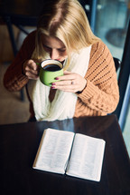a woman reading a Bible and drinking coffee