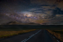 stars in the night sky above a road