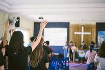 people with hands raised during a worship service