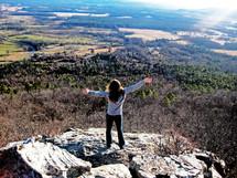 Girl standing on boulders overlooking fields in the valley