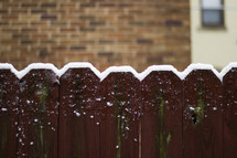 Snow on the top of a fence.