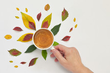 Espresso Coffee Cup with Autumn Leaves and Hand