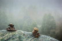 Two stacks of stones on the edge of a cliff.