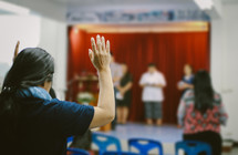 a woman standing with hands raised at a worship service