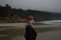 A young woman in a hat staring out at the ocean.