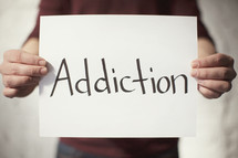 man holding a piece of paper with the word Addiction on it