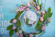 Easter cake in the center of a wreath of spring flowers on a blue vintage background