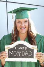 a graduate holding a thanks mom and dad sign