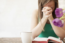 Woman with a coffee cup praying in the morning over the Bible on a wood table with flowers.