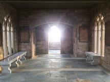 sunlight through the open doors of a stone chapel