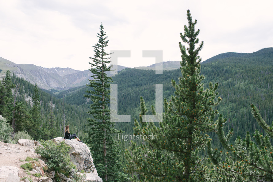 woman sitting on a mountainside cliff looking out