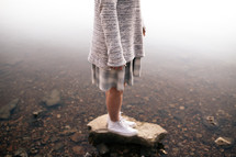 a girl standing on a stone in a pond