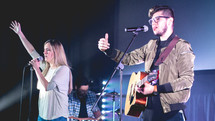 worship leaders singing into a microphone on stage