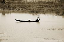 men fishing in a canoe