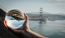 view of the Golden Gate Bridge through a glass orb