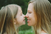 Smiling mother and daughter touching noses.