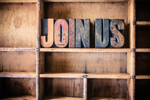 "Wooden letters spelling  ""join us"" on a wooden bookshelf."