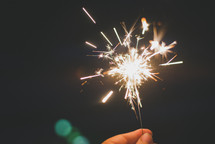 holding a sparkler and bokeh lights