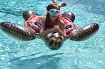 A little girl with goggles on a sea turtle pool float