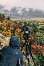 man with a camera filming from a mountain