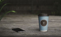 coffee cup with a cross on it and an iPhone