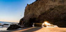 sunburst through a cave on a beach