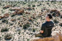man sitting on a rock looking out at a desert landscape