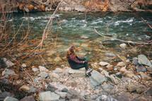 woman sitting on rocks along a riverbank