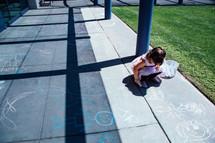 a child drawing with sidewalk chalk