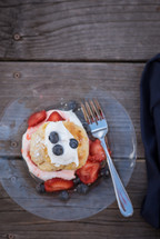strawberries and blueberries on pancakes