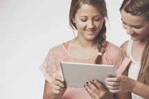 teen girls holding an iPad