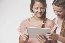 teen girls holding an iPad