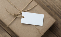 A white tag on a brown paper package tied with twine.