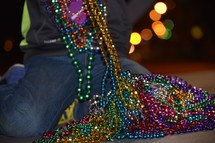 A little boy counting his beads after a Mardi Gras Parade